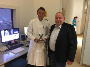 Drei Mal nacheinander gewann er den Spendenlauf – nun darf der markante Pokal in seiner Praxis bleiben: Dr. Michael Finkenstaedt bei der Übergabe durch Peter Beckelmann, dessen Firma die Spendenläufe seit 2015 ausrichtet.